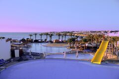 Free Blue Pool At Sunrise Or Sunset With A Yellow Slide. View From The Hill, A Beautiful Place To Relax In A Five Star Egypt Hotel. Royalty Free Stock Images - 172674459