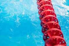 Blue pool water and red swimming lane marker in swimming pool with sun reflections. Abstract pattern. Blue pool water and red swimming lane marker in swimming royalty free stock photography