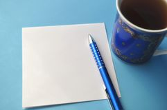 Blue porcelain china cup with blue pen and pencils, white note card and blue background Stock Image