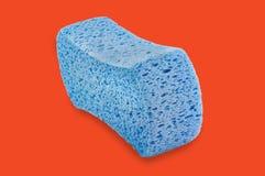 Blue porous sponge in center on orange royalty free illustration