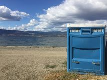 Blue port a potty on lake shore. Blue port a potty toilet on beach with lake and mountains in background. Gravel trail and lake shore with grass stock photo