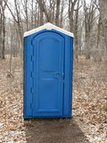 Blue Porta Potty in a woods Stock Image