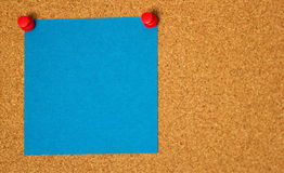 Blue post-it on a coarkboard background Royalty Free Stock Photo