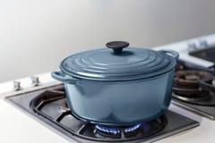 BLUE POT ON A GAS STOVE. Cooker steel stove up saucepan burn fire pan hob closeup burner butane fuel cook oven kitchen tongues soup black Stock Image