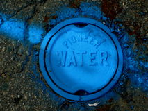 Blue pot hole cover. A pot hole cover with hand recesses in a dark gray surface (road perhaps) with access to the water main sprayed with blue paint Royalty Free Stock Photo