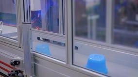 Blue pots on conveyor belt of plastic injection molding machine with robotic arm