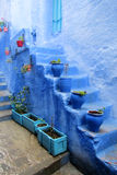 Blue pots at the stairs in Chefchaouen, Morocco. Blue pot with purple flower in blue city. Blue city Chefchaouen street. Chefchaouen or Chaouen city in Morocco Royalty Free Stock Images