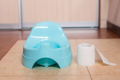 Blue potty with toilet paper. Blue baby pot with toilet paper on the floor in the bathroom royalty free stock photography