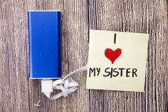 a blue power bank charging with white data cable kept on the wood table and written on the page i enormously love my sister that h stock image