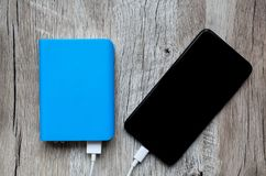 Blue power bank with white usb and black smartphone on wooden ba royalty free stock photography