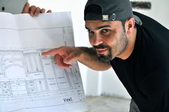 Blue print. This picture represents a construction man explain the blue print details for the kitchen cabinets design Stock Photography
