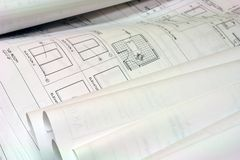 Blue Print Building Plans. Close up of blue prints unrolled on desk Stock Images