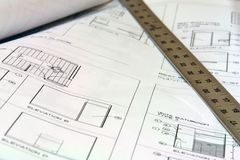 Blue Print Building Plans with Ruler. Close up of blue prints with metal ruler Royalty Free Stock Image