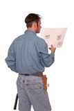 Blue prints. Carpenter reading blueprints with back to the camera Royalty Free Stock Photography