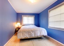 Blue purple bedroom with white blanket. Stock Photos
