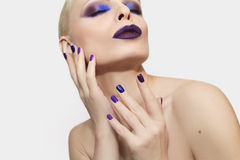 Blue purple fashion multicolored manicure and makeup . Blue purple fashion multicolored manicure and makeup on the blonde woman on gray background stock photos
