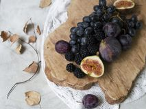 Blue and purple food. Blackberries, grapes, plums, blueberries, figs on a wooden background royalty free stock images