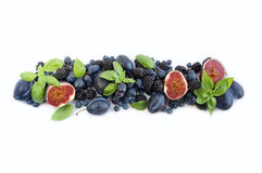 Blue and purple food. Top view. Ripe blueberries, blackberries, grapes, plums and figs. stock image