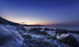 Blue purple sunset on beach. Rocks on sea. stock image