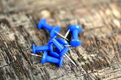 Blue push pins on old wooden background Royalty Free Stock Image