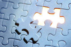 Blue Puzzle. A blue jigsaw puzzle missing one piece with golden light showing through Royalty Free Stock Photography