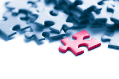 Blue puzzle with one pink piece Stock Images