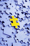 Blue puzzle with one yellow element stock images