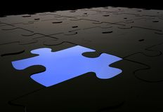 Blue puzzle piece amongst black pieces Stock Photo
