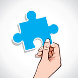 Blue puzzle piece on hand Stock Photos