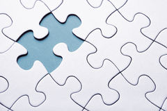 Blue puzzle piece missing. On white background stock photo