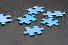 Blue Puzzle Pieces. Six blue puzzle pieces placed randomly on a black leather background Royalty Free Stock Image