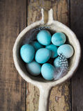 Blue Quail Easter eggs and feathers in a dipper made of clay Royalty Free Stock Photo
