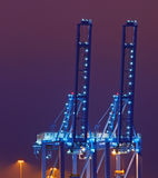 Blue quay cranes at night. Container cranes in the Port of Rotterdam against purple night sky Stock Photos
