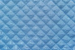 Blue quilted synthetic fabric with grained texture Royalty Free Stock Photos