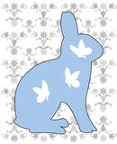 Blue rabbit. Illustration of a blue rabbit with butterflies and flower motive on the background Royalty Free Stock Photography