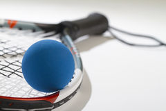 Raquetball on raquet strings. Blue racquetball in foreground laying on racquet strings. Handle is blurred Royalty Free Stock Photography