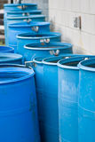 Blue rain barrels in a row flowing into each other Stock Image