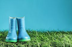 Blue Rain Boots sitting in the Grass. Blue children`s rain boots / wellies sitting in the grasss agaisnt a blue background with room for copy space stock photos
