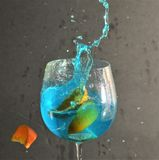 Blue Rasberry and Orange Slice Sparkling Splash. Blue Raspberry drink splashing out of a wine glass after three slices of oranges are dropped into the glass stock photo