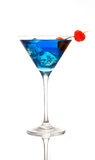 Blue raspberry cocktail. A blue cocktail in a martini glass with a raspberry Royalty Free Stock Images