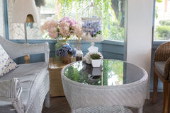 Blue rattan sofa with pillow in living room beside window with g Royalty Free Stock Images