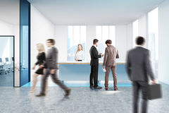Blue reception counter in white office, people. People walking near a blue reception counter standing in front of tall windows in a white office lobby with Royalty Free Stock Photos