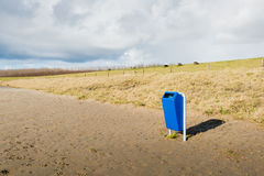 Blue recycle bin on an empty beach Stock Images
