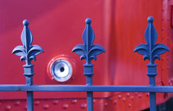 Blue and red. Blue metal fence posts on a red background Royalty Free Stock Photos
