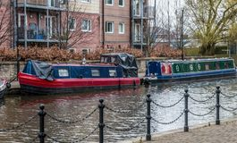 Blue and Red Barge and Green Barge. Two colourful barges moored up on the canal in Wigan. One blue and red and the other green Royalty Free Stock Image