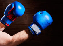 Blue and red boxing gloves on hands on brown background. Royalty Free Stock Photo
