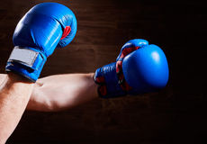 Blue and red boxing gloves on hands on brown background. Stock Photo