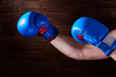 Blue and red boxing gloves on hands on brown background. Stock Image