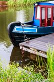 Blue and red canal boat moored in the Forth & Clyde Canal, Scotland stock photo