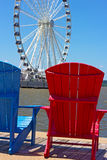 Blue and red chairs on a pier with Ferris wheel on background. Royalty Free Stock Image